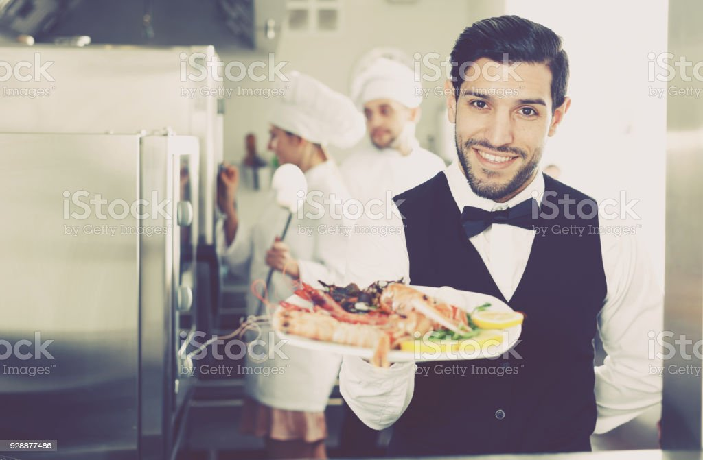 Waiter With Dish Of Seafood In Kitchen On Restaurant Stock Photo Download Image Now Istock