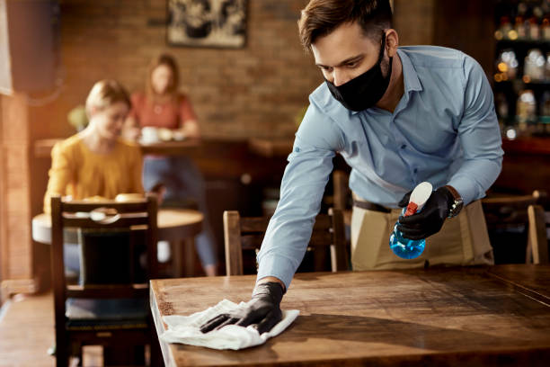 Waiter with protective face mask disinfecting tables in a pub. stock photo