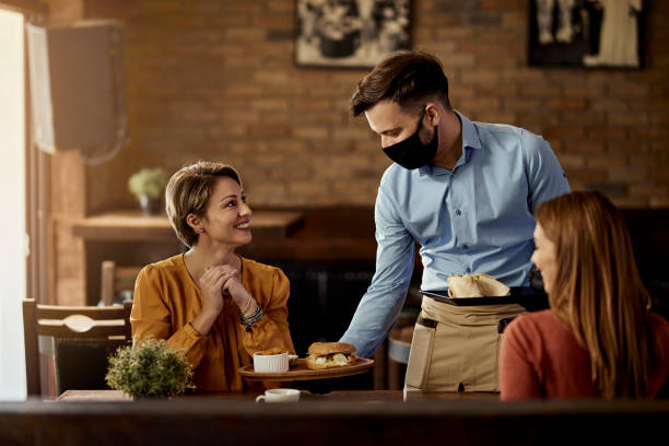 Waiter with protective face mask serving food to customers in a pub. stock photo