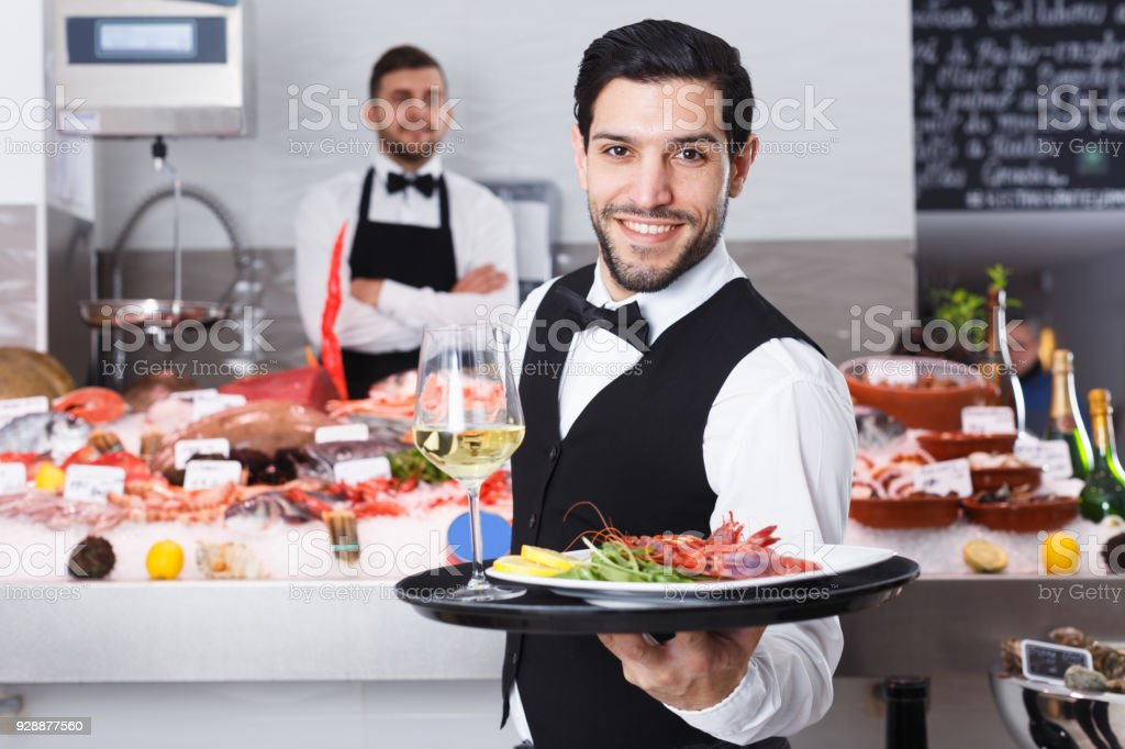 Waiter with serving tray in fish restaurant stock photo