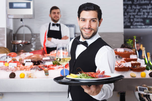 Waiter with serving tray in fish restaurant Portrait of smiling waiter with serving tray offering dishes in fish restaurant waiter stock pictures, royalty-free photos & images