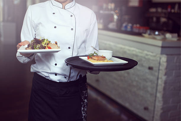 Waiters carrying plates with stock photo
