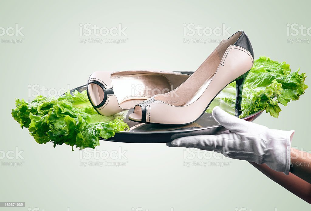 Waiter's hands holding female shoes on tray, with path royalty-free stock photo