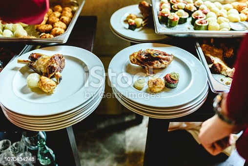 Waiters of a catering company plating the main course of a business lunch.