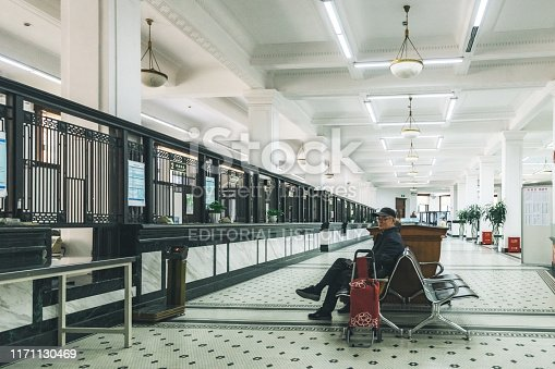 Shanghai, China - April 19, 2018: chinese man sitting on bench in the waiting area of the general post office building