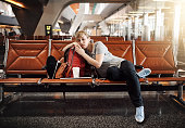 Full length shot of an attractive young woman sleeping in an airport