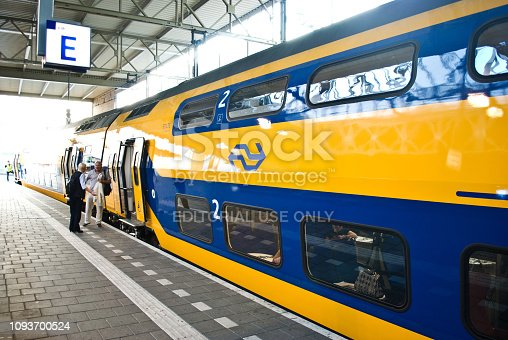 istock Waiting commuters/tourists at standing near a NS (Nederlandse Spoorwegen) train on platform E at Eindhoven railway station, the Netherlands 1093700524