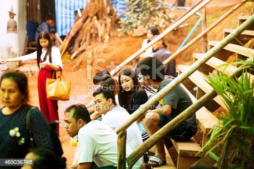 Amphoe, Thailand - February 26, 2015: Capture of young Thai people sitting on steps on mountain Khao Khitchakut in Amphoe, Chanthaburi. On top is rock with shrine and buddhas footprint and temple. Thai have been on top in night there for night procession. After some hours walk they are waiting on lower altitude for 4x4 service down to valley. Sunrise and electric light atmosphere.