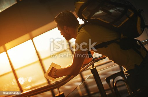 Closeup side view of a late 20's man with a backpack waiting for his flight at a first class lounge at an airport. He's looking at the beautiful sunset in the background. He's holding UK passport and a generic flight ticket with no data on it.