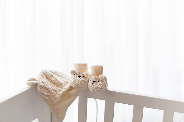 Waiting for a new life begining. Knitted hat and booties. stock photo
