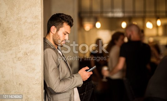 Shot of a young man using mobile phone while standing in a bar
