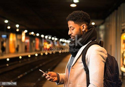 A man checking his phone as he waits for a subway train at a Paris Metro station.