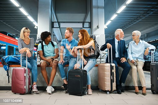 Closeup front view of group of young adults and a senior couple waiting for a train ride at an underground railroad station. They are sitting on a bench and talking.