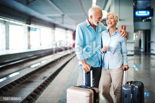 Closeup of an early 60's couple waiting for a train at a train station. They are standing on the platform with suitcases on the side, the man emraced his wife, they are talking and laughing. Copy space on the left.