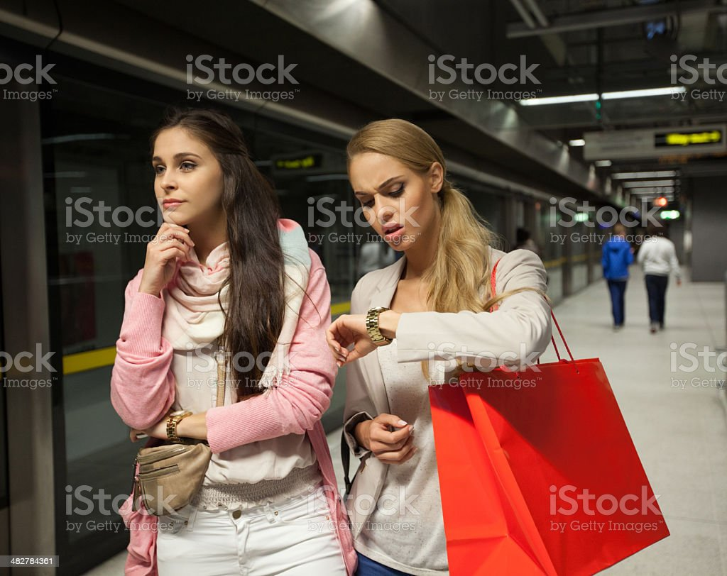 Waiting for a train Two worried young women waiting for a train at subway station.   20-24 Years Stock Photo