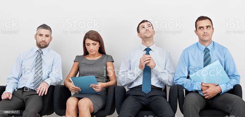 Waiting for an interview Four business people sitting on chairs in a row and waiting for an interview. Adult Stock Photo