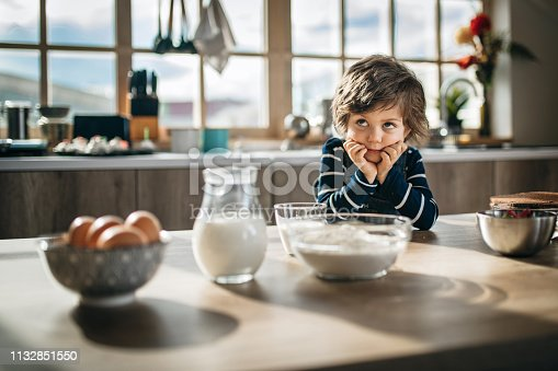 Young boy waiting for breakfast at kitchen table