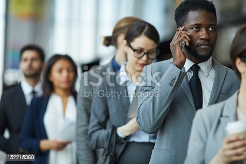 Serious displeased young African-American businessman with beard standing in line and calling on mobile phone while waiting for business forum registration