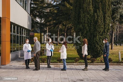 Group of senior, mid and young adult people with protective face masks standing in a line in front of a hospital and waiting for coronavirus vaccination, while young female doctors giving them explanations and directions