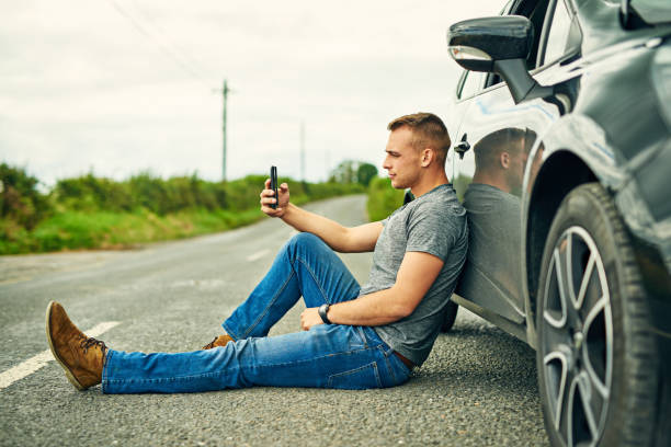 Waiting for his wheels to be towed away Shot of a young man waiting for roadside assistance after breaking down aground stock pictures, royalty-free photos & images