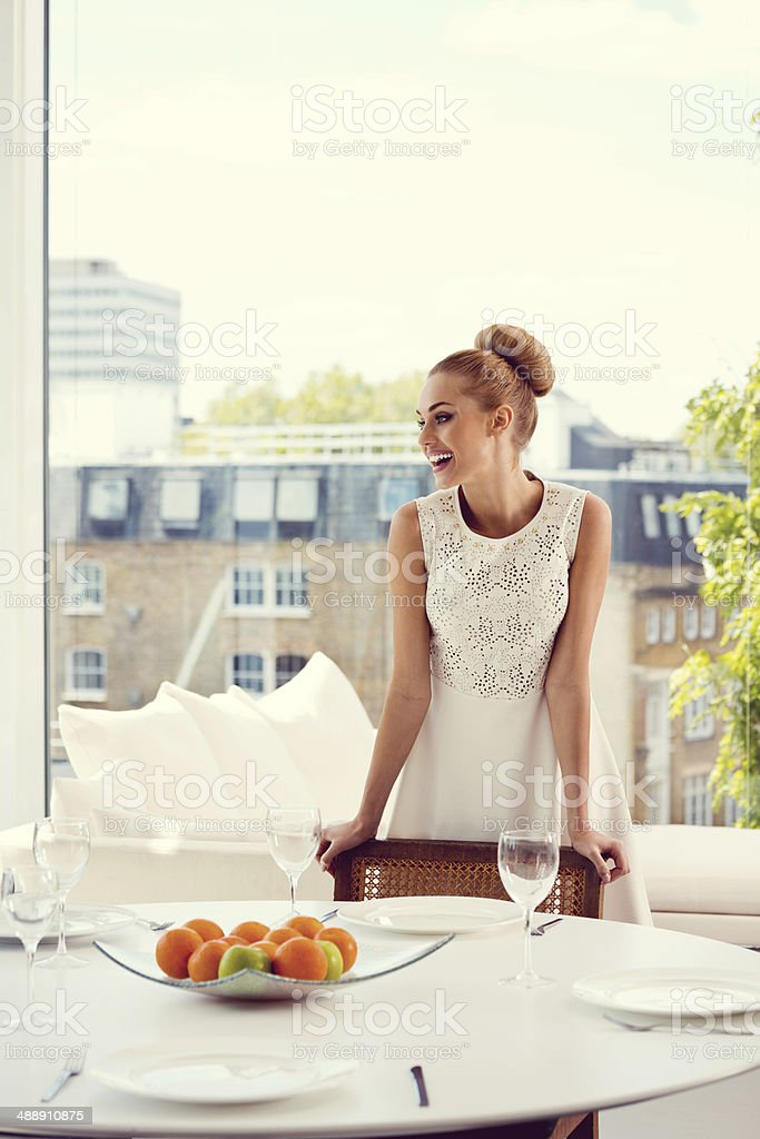 Waiting for lunch Elegant woman standing at dining table in her posh apartment and waiting for the guests. One Woman Only Stock Photo