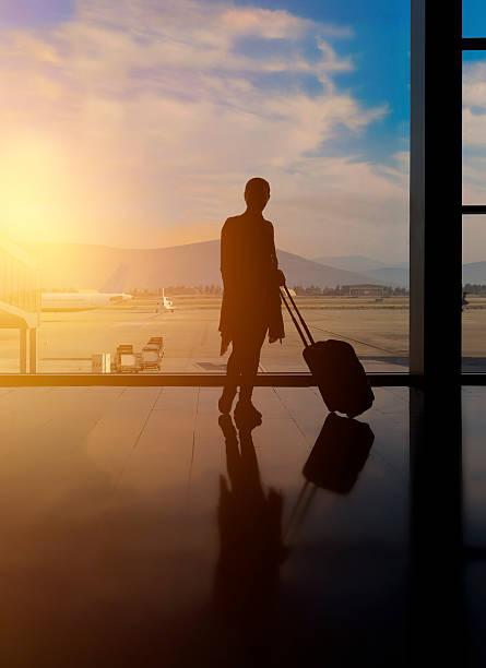 attesa per il mio volo - donna valigia solitudine foto e immagini stock