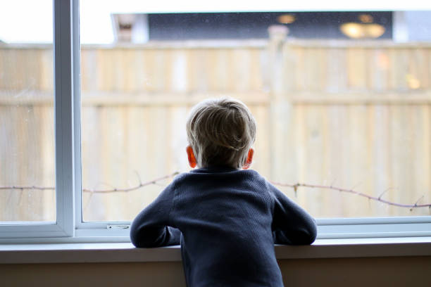 waiting for spring - boy looking out window stock pictures, royalty-free photos & images