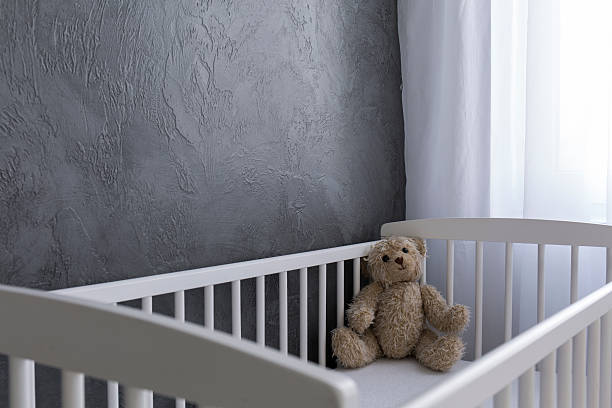 Waiting for the baby Shot of a teddy bear sitting in a crib crib stock pictures, royalty-free photos & images