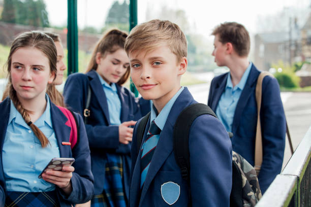 Waiting for the Bus Teenage school boy looking at the camera, standing at bus stop with friends. schoolboy stock pictures, royalty-free photos & images