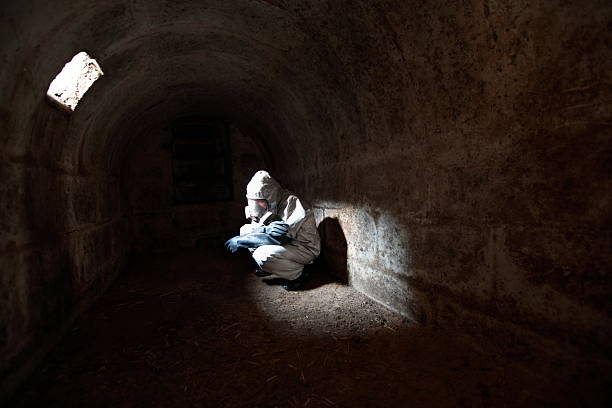 waiting for the end of  world in stone bunker man in gas mask and protective uniform waiting for the end of the world in stone bunker bomb shelter stock pictures, royalty-free photos & images