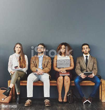 Studio shot of a group of businesspeople looking bored while waiting in line to be interviewed against a gray background