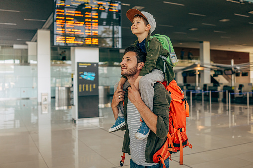 Photo of a cheerful little boy and his father, who travel together waiting for their flight at the airport