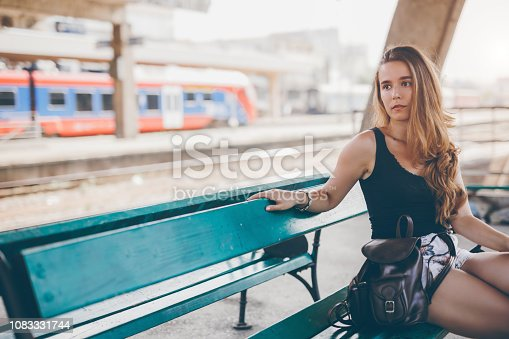 Young woman waiting for the train on a railway station