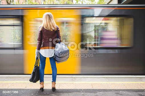 Rear view of a young hipster style woman holding a couple of bags while waiting for the train. A yellow and grey train can be seen moving in front of her in a blur.