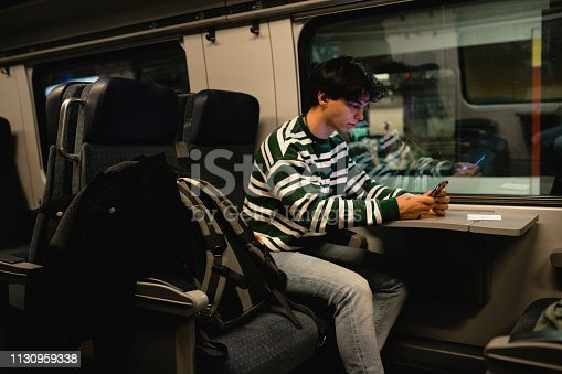 Young male adult using his smart phone while sitting on a train. He is waiting for the train to depart from the station.