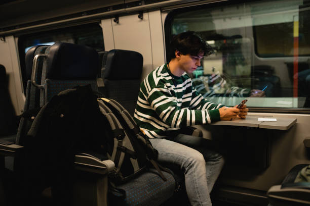 Waiting for the Train to Depart Young male adult using his smart phone while sitting on a train. He is waiting for the train to depart from the station. depart stock pictures, royalty-free photos & images