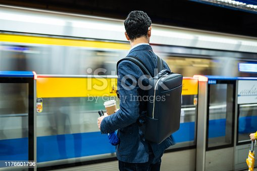 Rear view of handsome man waiting fr train at subway, holding bag on his back and cup of coffee