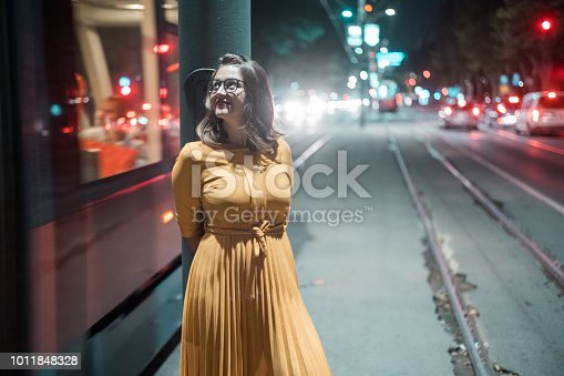 Young woman standing on the trolley station at night