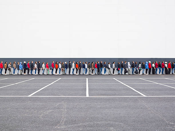 Waiting in Line Large group of people waiting in line people in a row stock pictures, royalty-free photos & images
