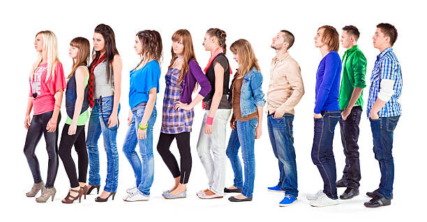 Waiting In Line Large groupe of young adult people standing in a row and waiting for something. Studio shot on the white background. people in a row stock pictures, royalty-free photos & images