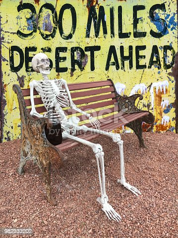 Composite image of an old road sign behind a human skeleton sitting on a park bench. Northern Arizona.