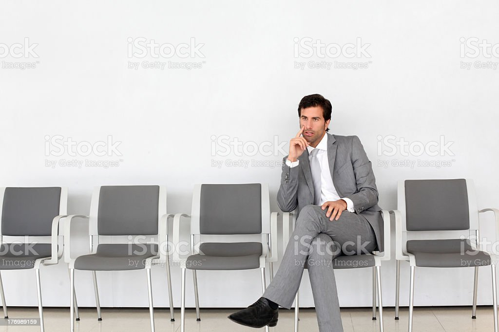 A waiting man in suit sitting in an empty row of gray chairs stock photo