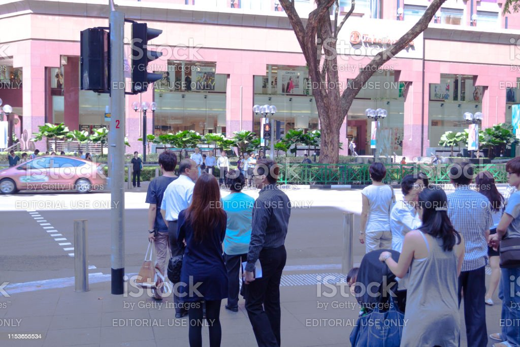 Waiting people at traffic light and crosswalk on Orchard Road in...