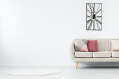 Waiting room in a modern office with metal clock on white, empty wall and beige couch with pink pillows
