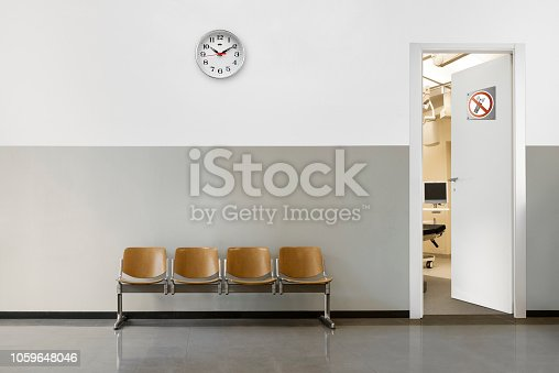 empty waiting room with chairs, clock on wall and open door with phone off symbol