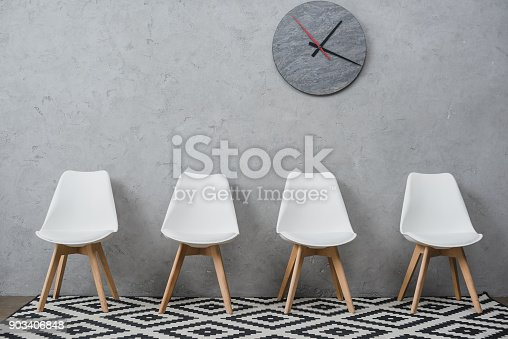 Row of empty white chairs in a waiting room at company with wall clock