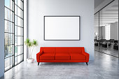 Waiting room with empty picture frame and red sofa