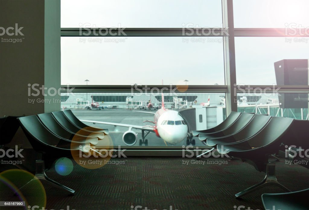 Waiting seats at airport with airplanes in window view stock photo
