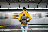 Young Caucasian woman with backpack waiting for a subway train.