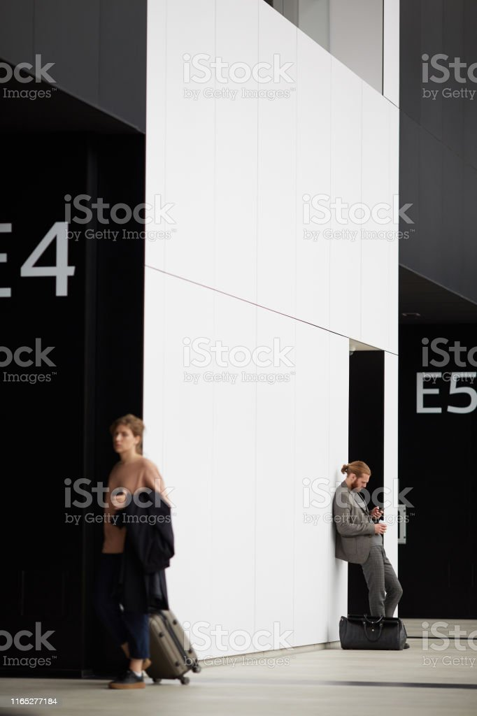 Serious bearded man in gray suit leaning on wall and using smartphone...